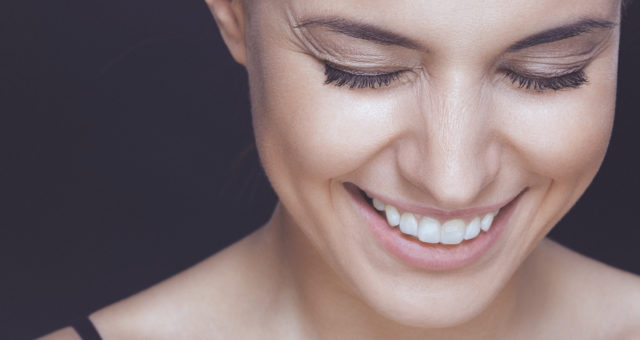 A close-up beauty portrait of a smiling young woman with closed eyes. There are visible wrinkles around her eyes and mouth. The woman has healthy, clean skin, natural make-up and dark hair that is swept back from her face. The woman's shoulders are shirtless and visible, and she is isolated on a dark background. Developed from RAW; retouched with special care and attention; small amount of grain added for best final impression; ready made for print and web use;